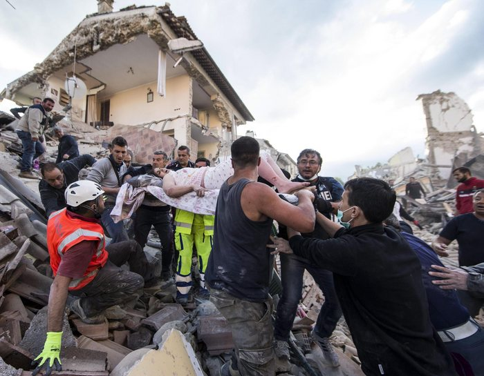 epa05603348 YEARENDER 2016 AUGUST  An injured woman (C) is carried by rescuers amid the rubble of collapsed buildings in Amatrice, central Italy, 24 August 2016, following a 6.2 magnitude earthquake, according to the United States Geological Survey (USGS), that struck at around 3:30 am local time (1:30 am GMT). The quake was felt across a broad section of central Italy, including the capital Rome where people in homes in the historic center felt a long swaying followed by aftershocks.  EPA/MASSIMO PERCOSSI