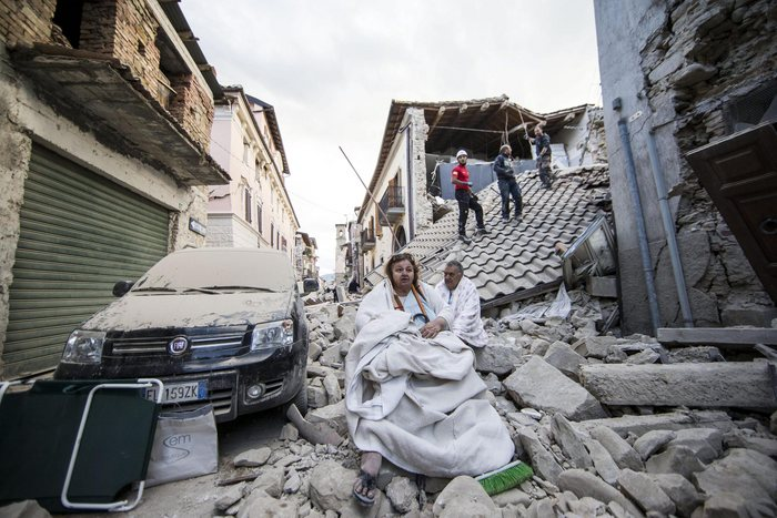 epa05603350 YEARENDER 2016 AUGUST  Residents look on as they stand on the rubble of collapsed buildings in Amatrice, central Italy, 24 August 2016, following a 6.2 magnitude earthquake, according to the United States Geological Survey (USGS), that struck at around 3:30 am local time (1:30 am GMT).  EPA/MASSIMO PERCOSSI