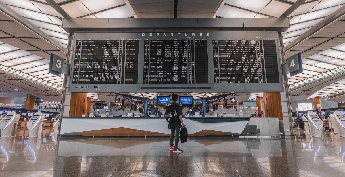 αεροδρόμιο επιβάτης μπροστά από οθόνη ανακοινώσεων πτήσεων