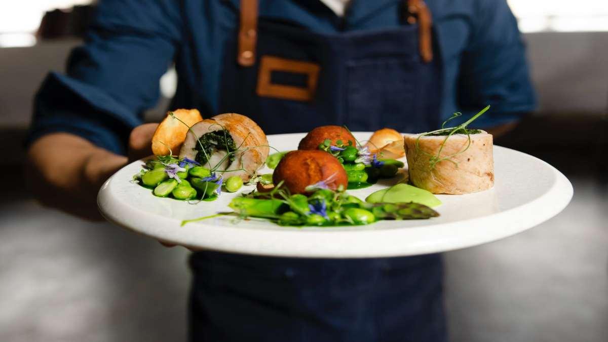 τάσεις γαστρονομία ξενοδοχεία 2021 σερβιτόρος με πιάτο φαγητό