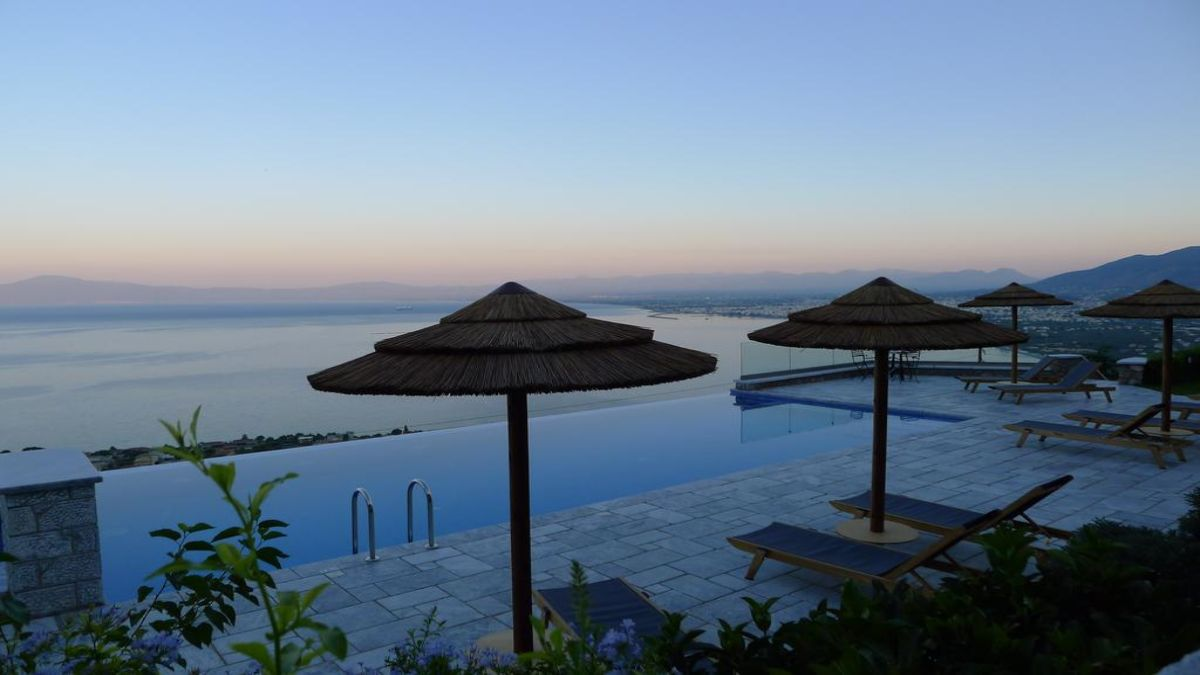 Petra Thea πισίνα με ομπρέλες το σούρουπο