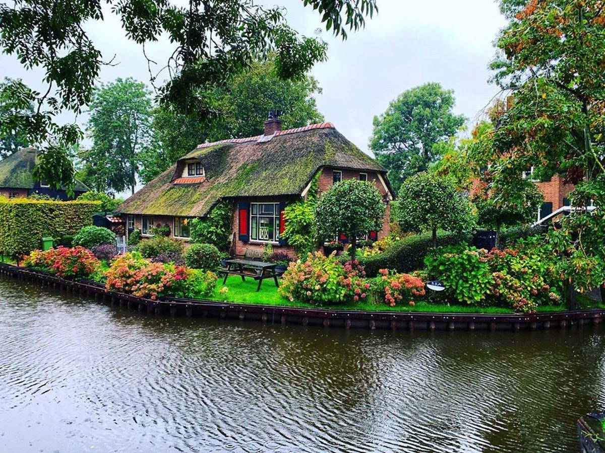 Giethoorn χωριό Ολλανδίας σπίτι σε ποτάμι με πράσινο κήπο