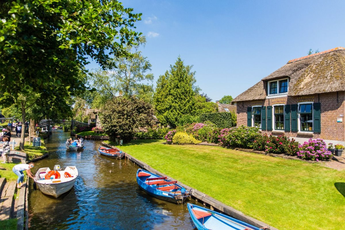 Giethoorn χωριό Ολλανδίας σπίτι σε ποτάμι με βάρκες για τους τουρίστες