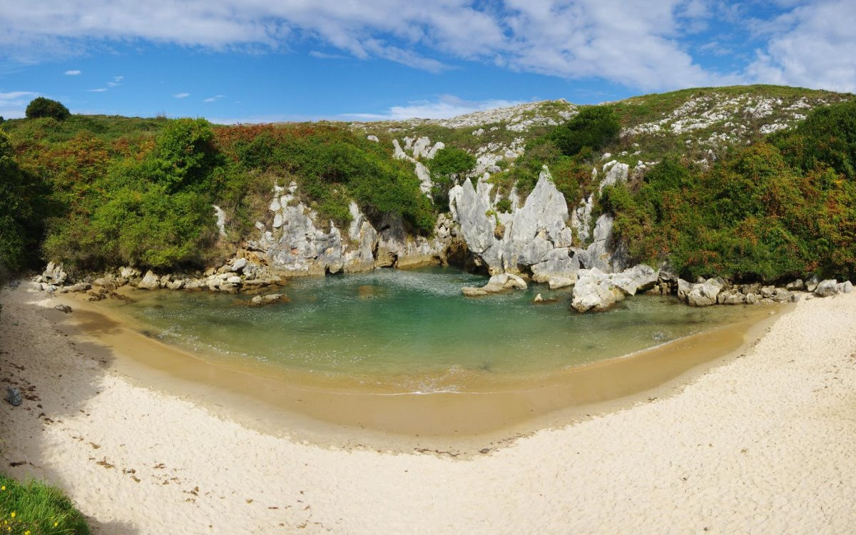 Gulpiyuri παραλία χωρίς τη θάλασσα με κατάφυτα βράχια ολόγυρα