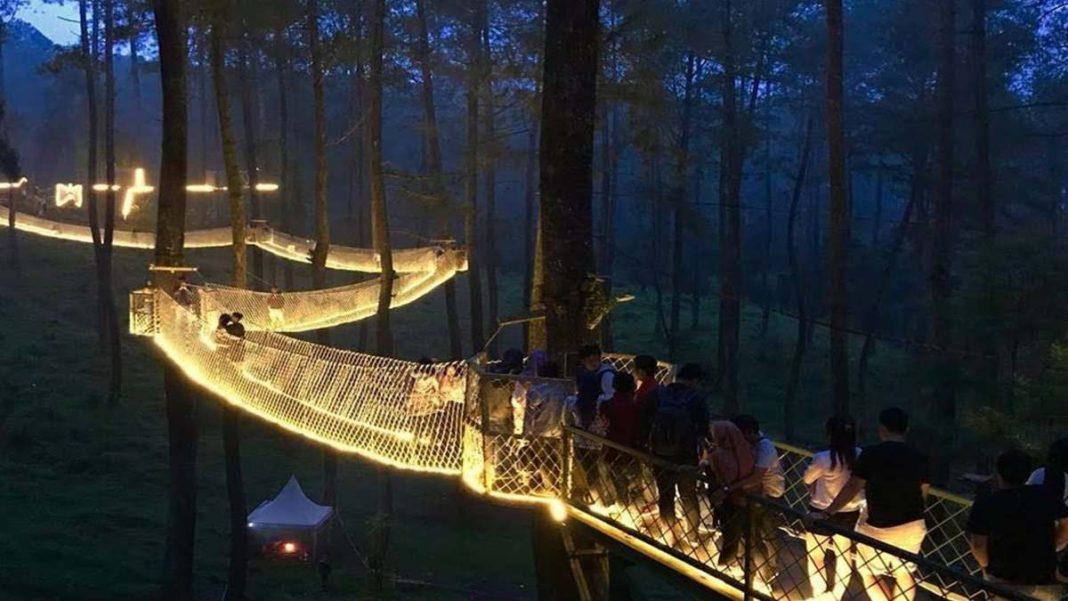 Ινδονησία φωτιζόμενη γέφυρα το βράδυ με τουρίστες