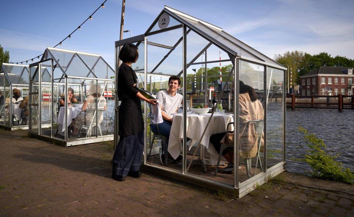 Εστιατόρια χειμώνας Mediamatic Αμστερνταμ με σπιτάκια και πελάτες με σερβιτόρο