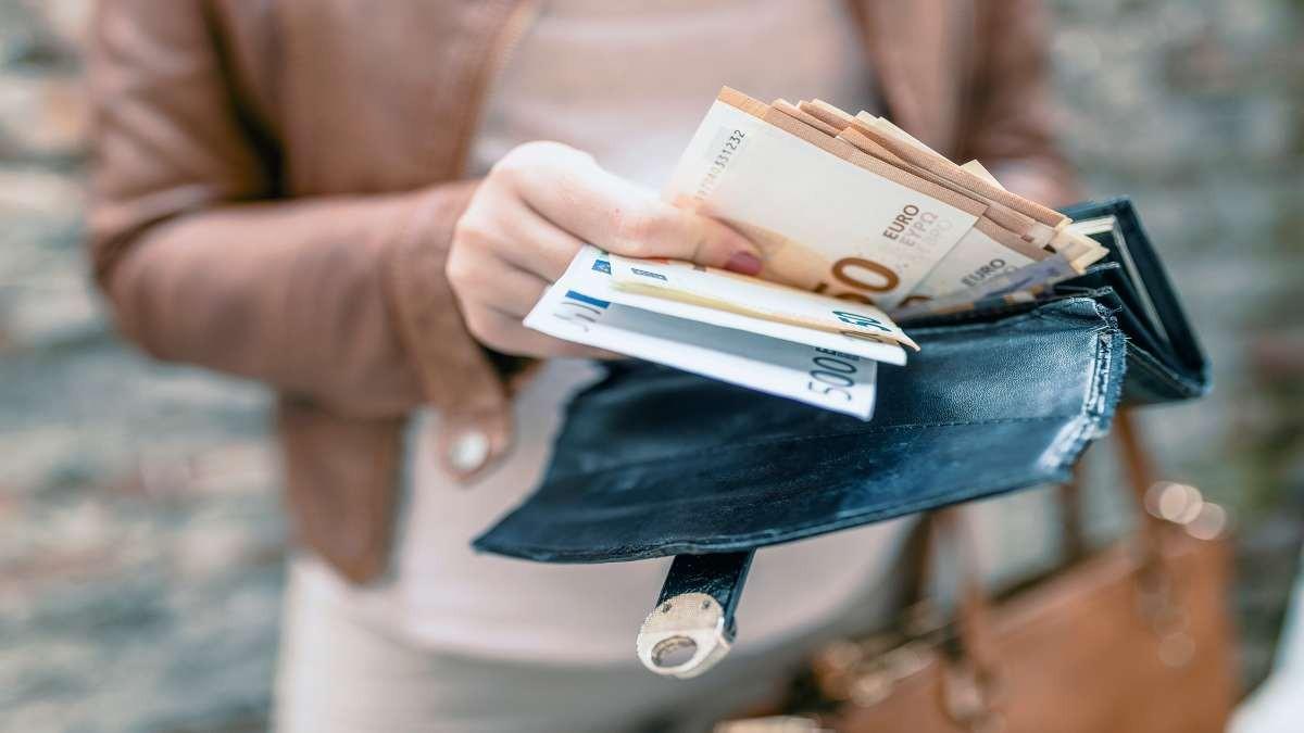 γυναίκα κρατάει χρήματα πορτοφόλι