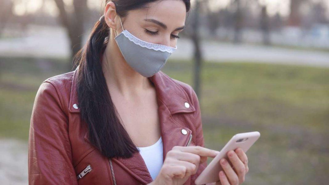 κοπέλα με μάσκα ψάχνει google στο κινητό