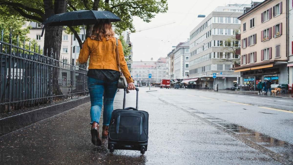 βροχερή μέρα κέντρο πόλης γυναίκα με ομπρέλα και βαλίτσα