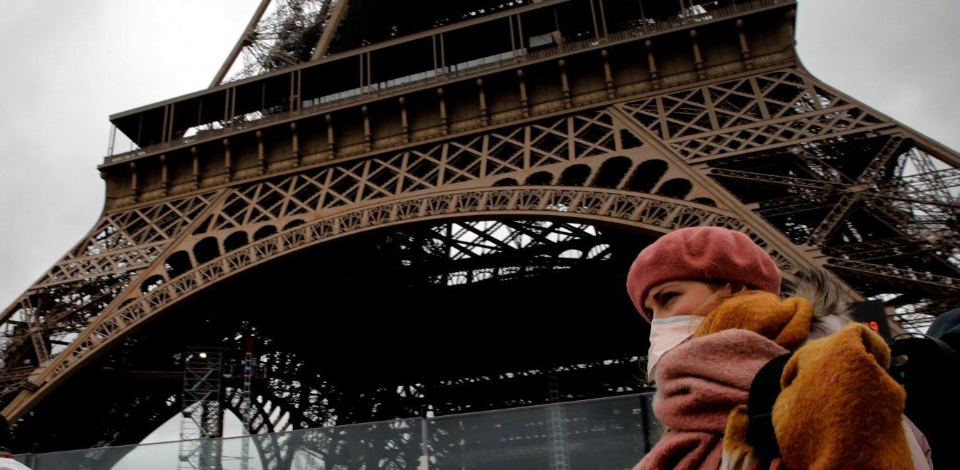 Κορονοίός Γαλλία Παρίσι κάτοικος με μάσκα μπροστά στο Πύργο του Άιφελ
