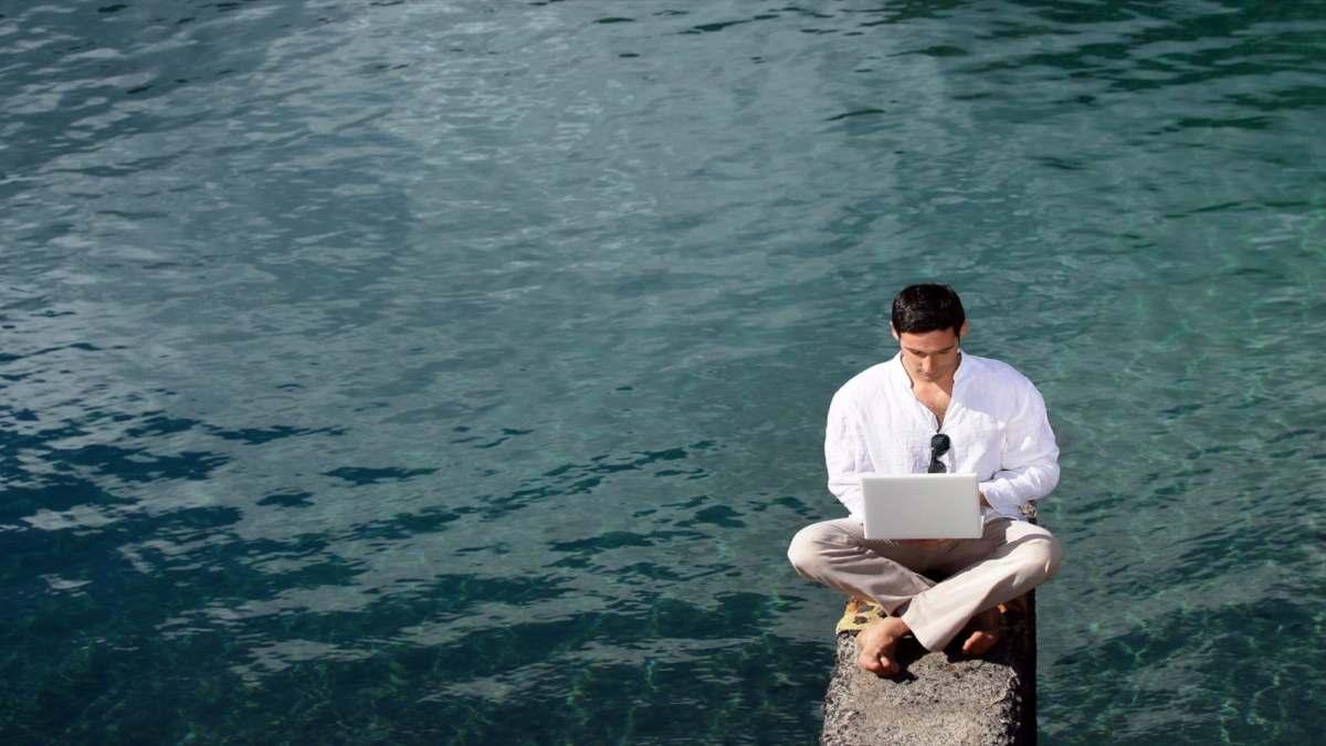 εργασία δίπλα στη θάλασσα με το λάπτοπ