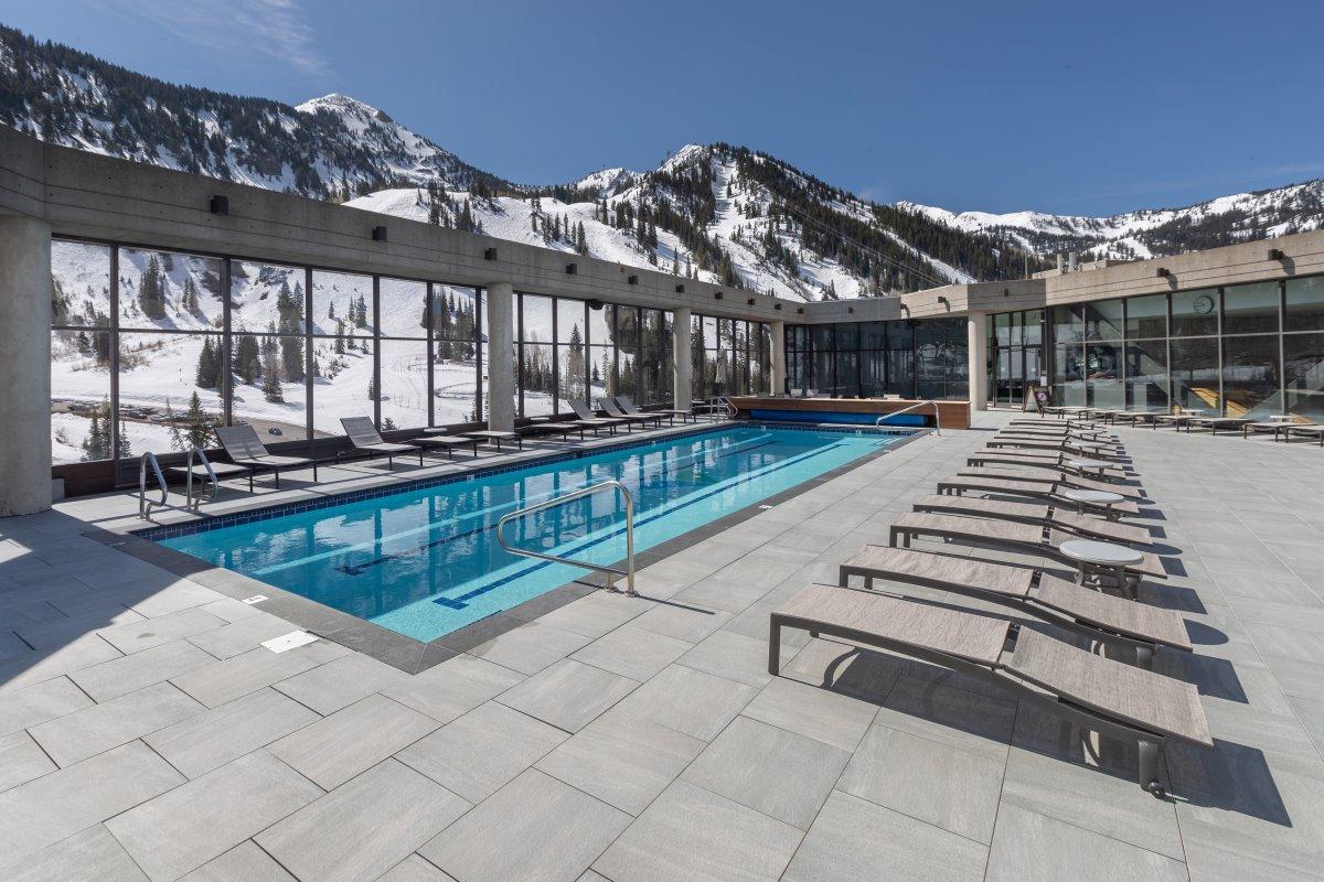 η εξωτερική πισίνα του Cliff Lodge & Spa με θέα στις χιονισμένες κορυφές