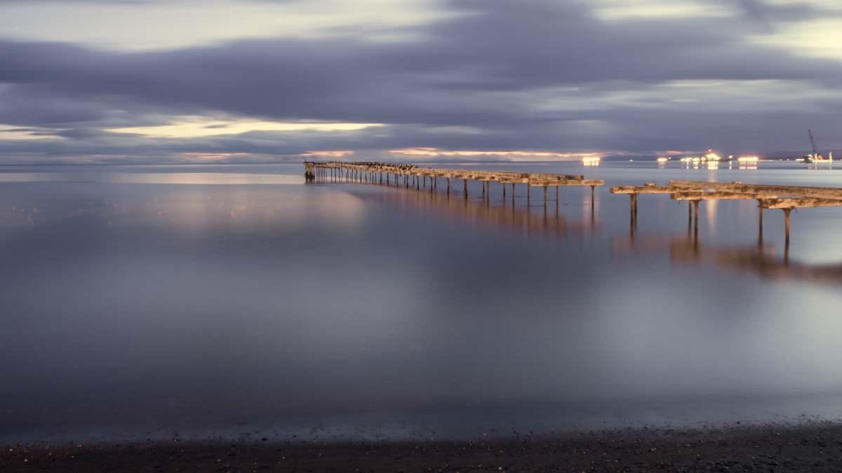 Παλαιά ξύλινη αποβάθρα στην Punta Arenas στη Χιλή στον Ειρηνικό Ωκεανό κατά τη δύση του ηλίου