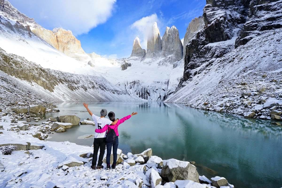 Ένα ζευγάρι ταξιδιωτών στέκεται κοιτάζοντας το Torres del Paine, μετά από μακρά πεζοπορία σε χιονισμένο μονοπάτι, στο εθνικό πάρκο Torres del Paine, Παταγονία, Χιλή.