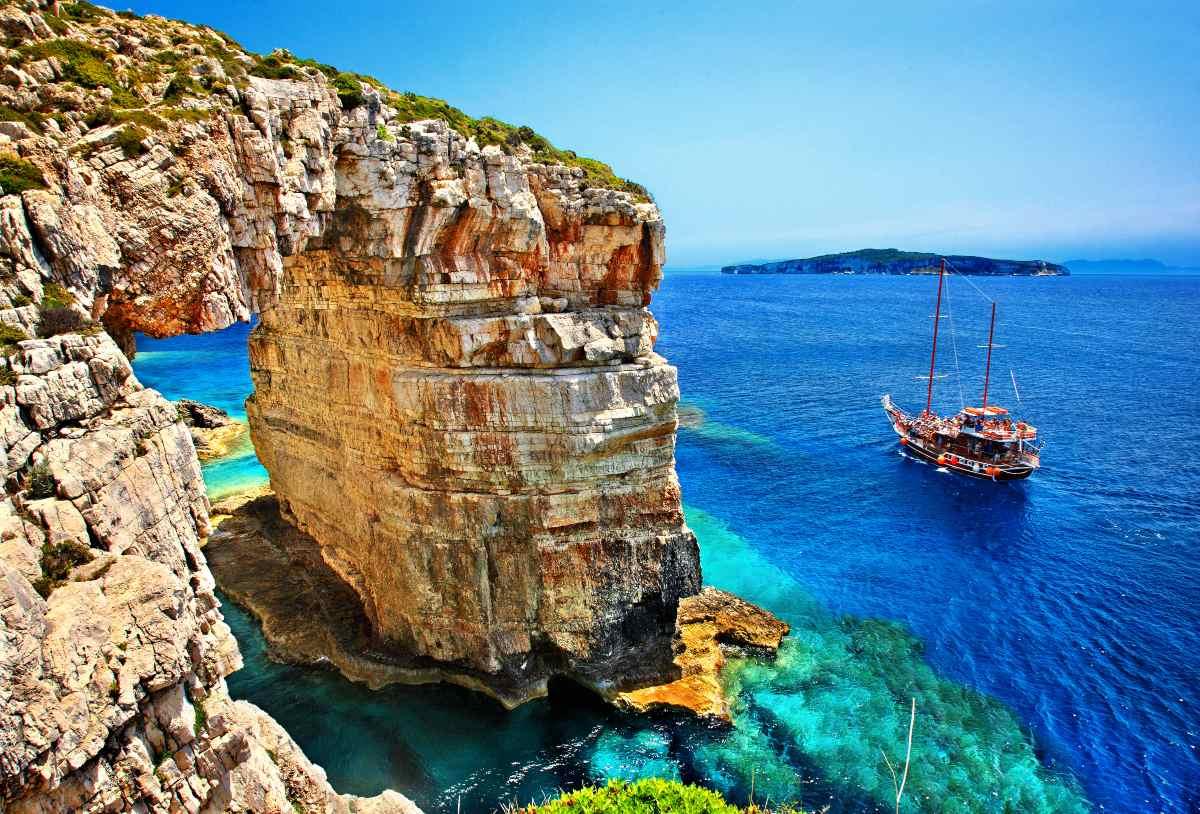 """Τουριστικό σκάφος που περνά δίπλα από τον Τρυπητό (γνωστό και ως """"Καμάρα""""), ένα φυσικό βραχώδες τόξο στους Παξούς. Στο βάθος, το νησί των Αντίπαξων."""